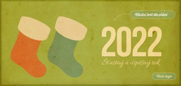 Retro novoročenka se dvěma vánočními punčoškami na zeleném strukturovaném pozadí zapůsobí nostalgií.