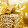 Zlatý, luxusně zabalený dárek v pozadí zlatých slavnostních dekorací vytváří výjimečné vánoční přání.