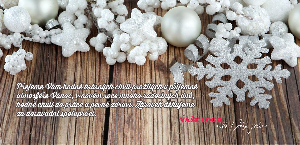 Vánoční zátiší s bílými ozdobami příjemně barevně kontrastujícími s dřevěným pozadím novoročenky