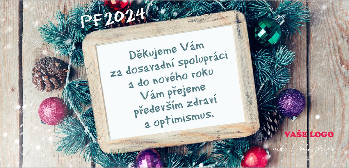 Firemní novoročenka s dřevěnou tabulkou na text přání obklopená chvojím s barevnými vánočními baňkami.