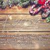 Přírodní chvojí ozdobené šiškami a stylovými vánočními ozdobami na dřevěném pozadí novoročenky.