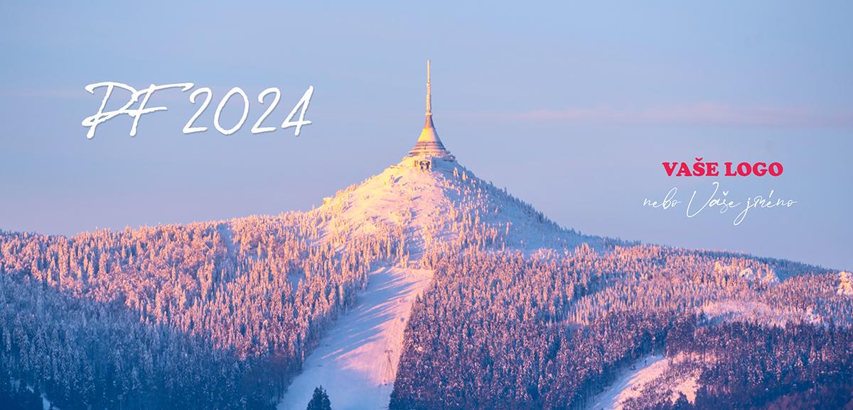 Firemní novoroční přání se zimní krásou zasněženého Ještědu ozářeného slunečními paprsky.