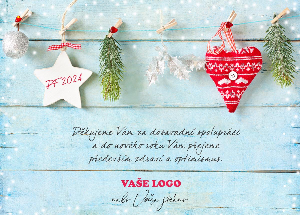 Originální vánoční přání s ozdobami a větvičkami rozvěšenými na provázku.